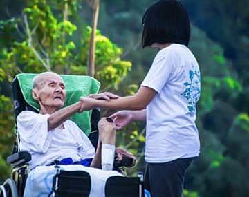 caregiver holding hands of an elderly patient on wheel chair