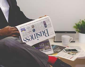 A business immigration person in a grey suit is reading the business section of the newspaper.