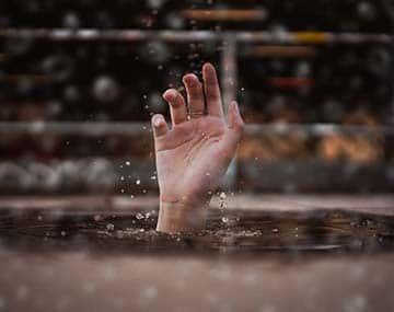 A drowning man's hand representing humanitarian & Compassionate (H&C) need