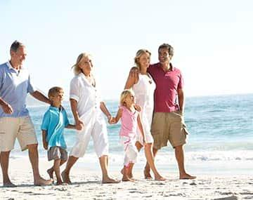 Parents and grandparents on super visa are walking on beach with children